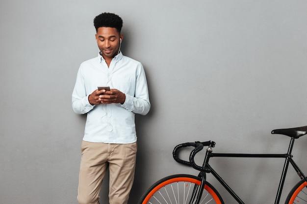 Человек, стоящий рядом с велосипедов в чате по телефону.