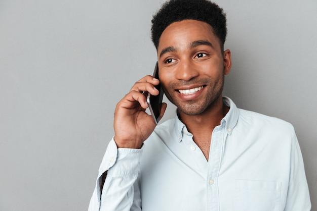 話している笑顔の若いアフリカ人の肖像画を間近します。