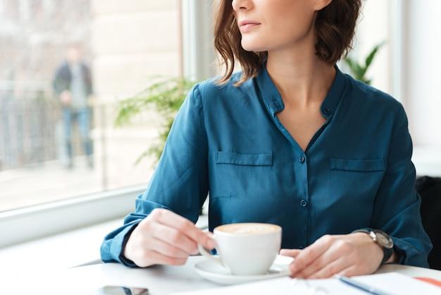 カフェで一杯のコーヒーを持つ若い女性