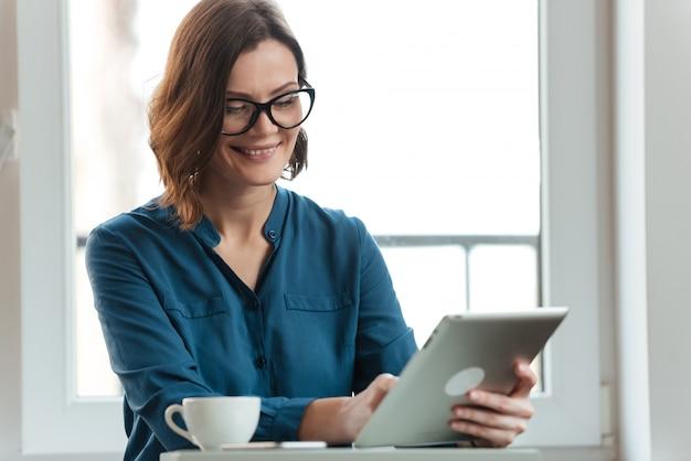 タブレットを使用して眼鏡の笑顔の女性