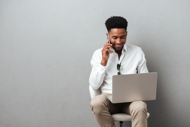 Молодой африканский мужчина держит ноутбук на коленях
