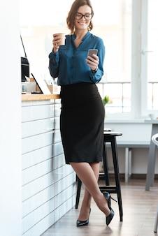 Женщина в очках, стоя с чашкой кофе в кафе