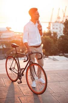 Сконцентрированный молодой африканский человек рано утром с велосипедом