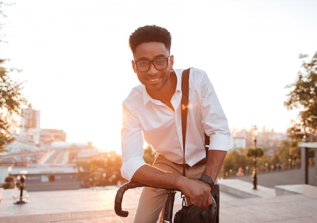 Счастливый молодой африканский человек рано утром с велосипедом