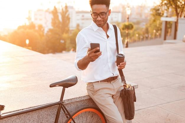 Африканский человек рано утром стоит возле велосипеда