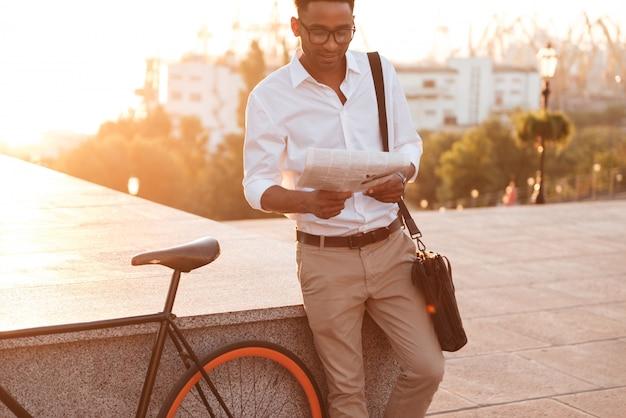 Красивый молодой африканский человек рано утром с газетой чтения велосипеда.