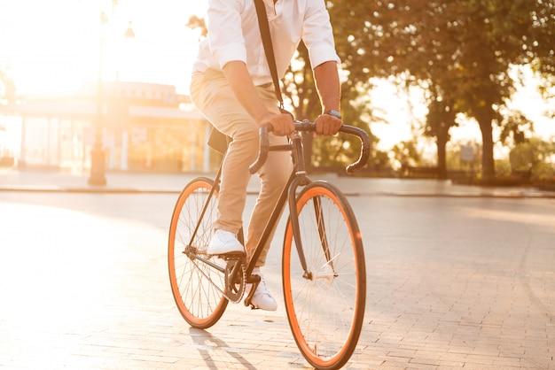 Красивый молодой африканский человек рано утром с велосипедом