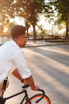 Молодой африканский человек рано утром с велосипедной прогулкой