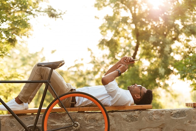 タブレットを使用して屋外自転車で早朝の若いアフリカ人