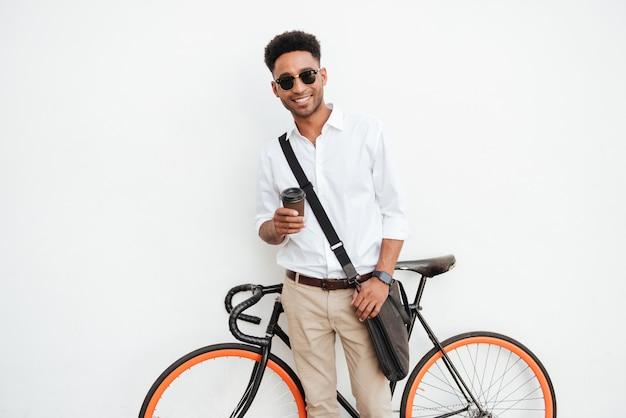 コーヒーを飲みながら自転車を持つ男。