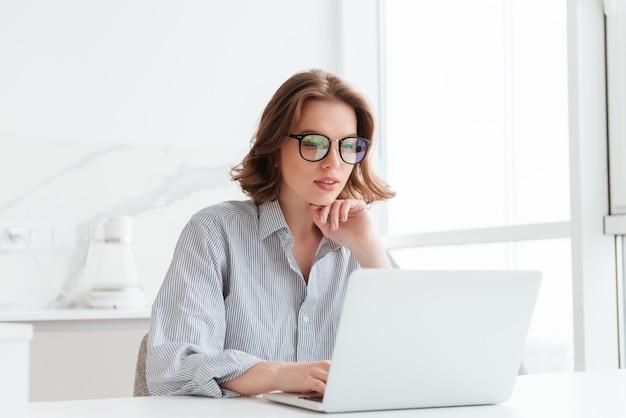 メガネとストライプシャツの魅力的な女性実業家が自宅に座ってラップトップコンピューターでの作業