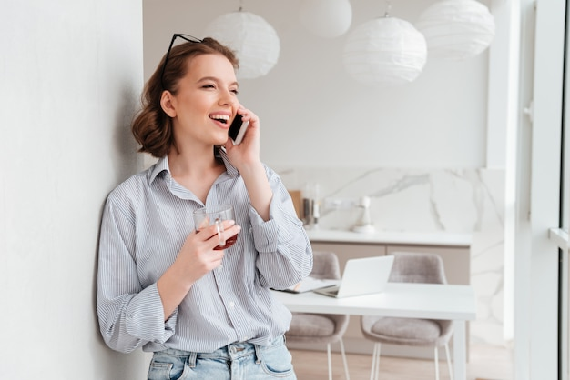 Портрет счастливой взволнованная женщина разговаривает по мобильному телефону