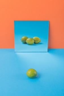 オレンジに分離された青いテーブルにライムします。