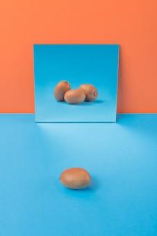オレンジに分離された青いテーブルのキウイ