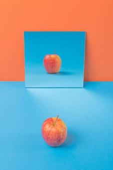 Яблоко на синем столе, изолированное на оранжевом