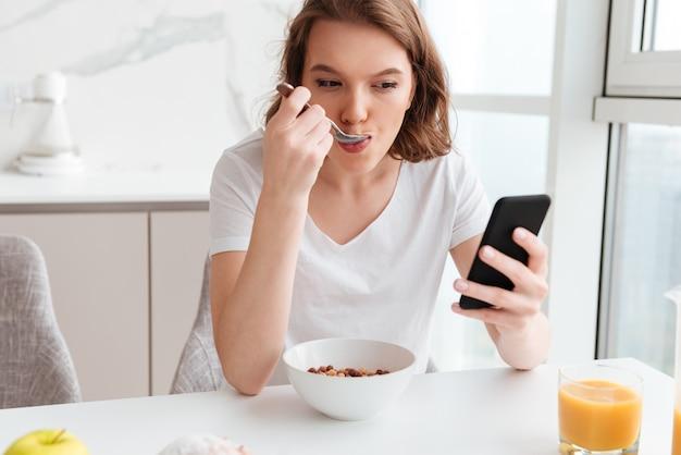 Портрет конца-вверх красивой женщины беседуя на мобильном телефоне пока ел кукурузные хлопья на кухонном столе