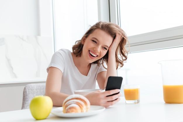 Портрет смех женщины в белой футболке, проверка новостей на мобильном телефоне, сидя за кухонным столом