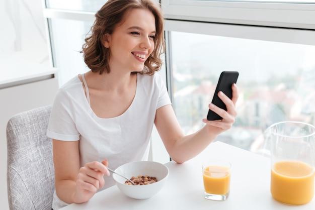 Портрет милой улыбающейся женщины в белой футболке в чате на смартфоне, сидя и есть кукурузные хлопья за кухонным столом