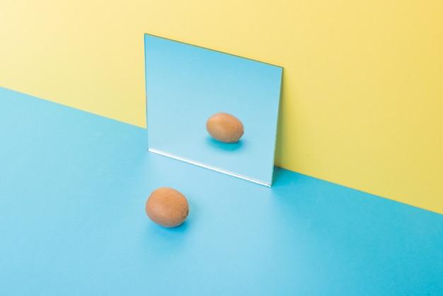 ミラーの近くの黄色に分離された青いテーブルのキウイ