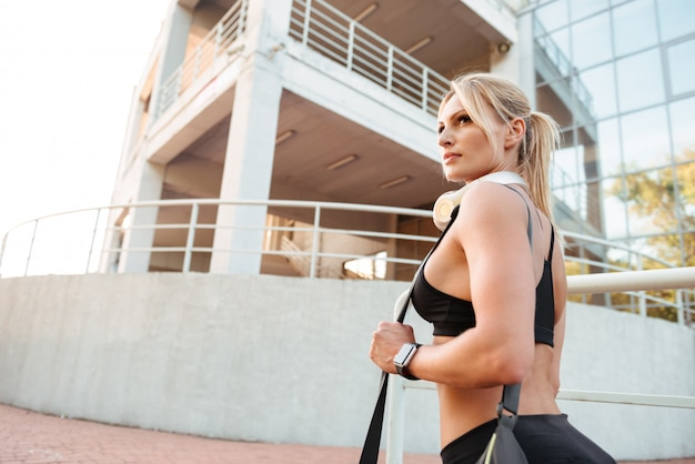 屋外に立っている強い若いスポーツ女性