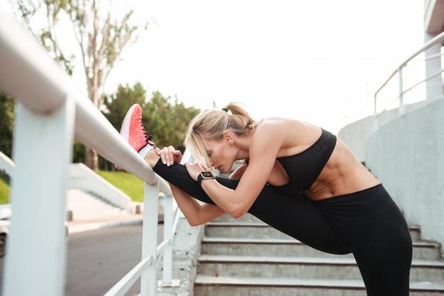 強い若いスポーツ女性はストレッチスポーツを作る