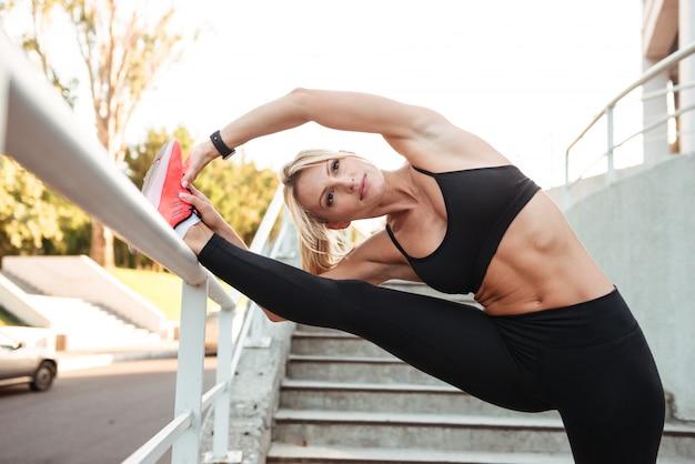 驚くほど強力な若いスポーツ女性のストレッチ