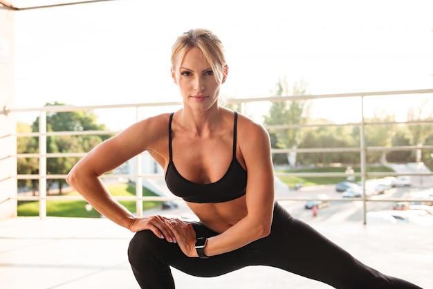驚くほど強力な若いスポーツ女性は、スポーツのストレッチ体操を行います。
