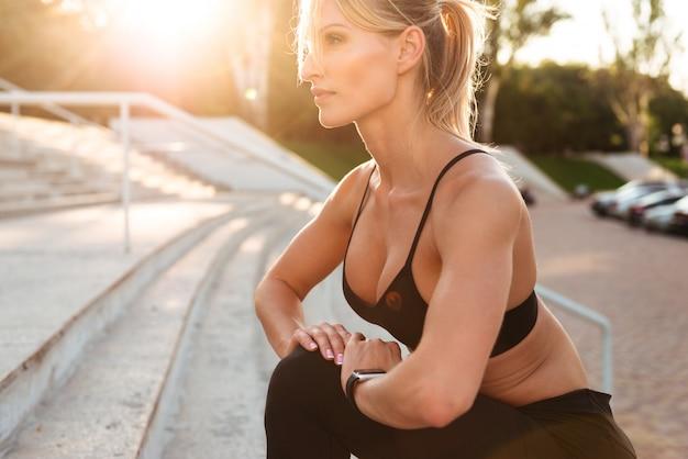 強力な若いスポーツ女性は、スポーツストレッチ体操を行います。