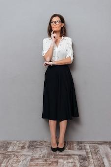 Полная длина картина задумчивой женщины в очках и деловой одежде, держа палец возле подбородка и глядя на серый