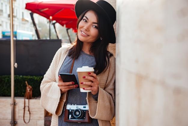 街の通りに立っている間、カメラを見て、スマートフォンとテイクアウトのコーヒーを保持しているスタイリッシュな摩耗で陽気なアジアの女性