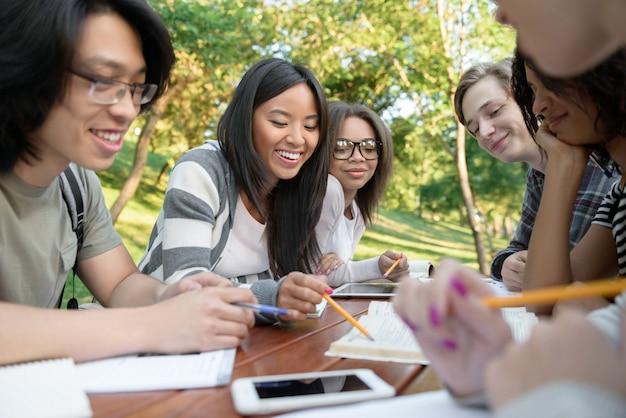 座っていると話しながら屋外で勉強する若い学生