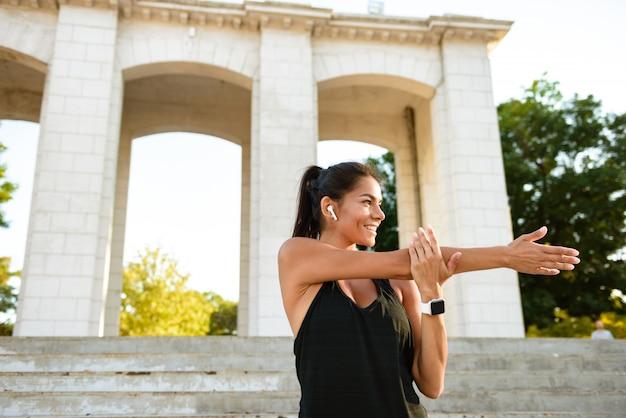 Портрет веселой фитнес-женщины в наушниках