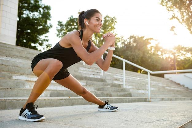 Портрет улыбающегося фитнес женщина в наушниках