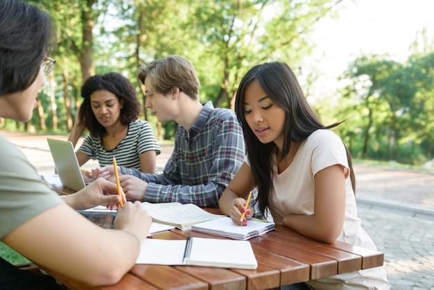 座っていると勉強している若い学生の多民族グループ