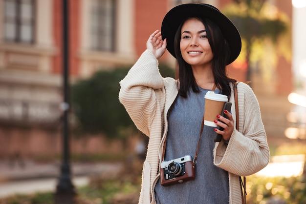 屋外で通りを歩きながらよそ見持ち帰り用のコーヒーと携帯電話を保持している黒い帽子の若い魅力的なアジアの女性