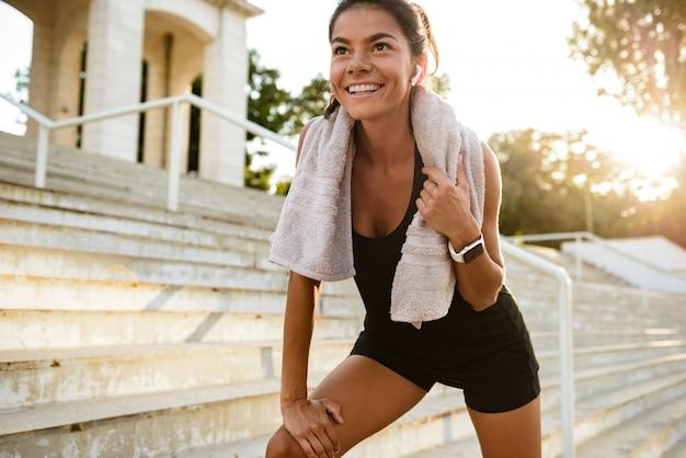 Портрет улыбающегося фитнес женщина с полотенцем отдыха
