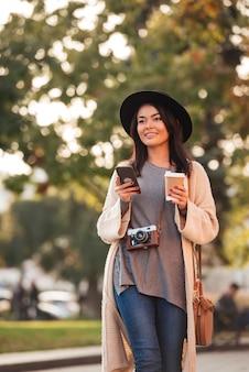 スマートフォンと屋外に行くコーヒーを保持しているスタイリッシュな服装で若い笑顔のアジア女性