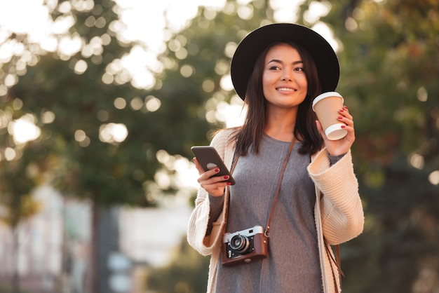 コーヒーを飲みながら屋外の公園を歩きながら携帯電話を保持している黒い帽子の若いアジア女性