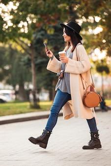 スマートフォンを使用して、屋外の公園を歩きながらテイクアウトのコーヒーを保持している現代のアジアの女性