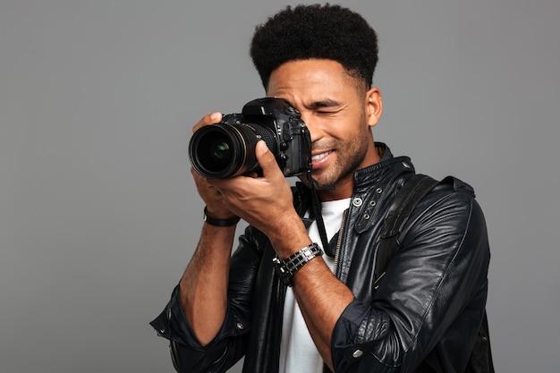 笑顔のアフロアメリカンの男性カメラマンの肖像画