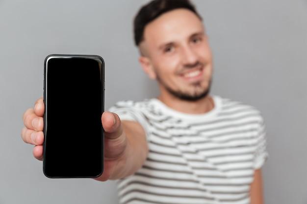 Веселый молодой человек, показывая дисплей мобильного телефона