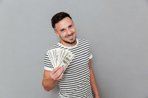 Улыбающийся человек в футболке держит деньги и смотрит в камеру