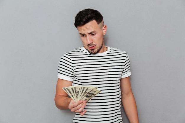 Шокированный мужчина в футболке держит и смотрит на деньги