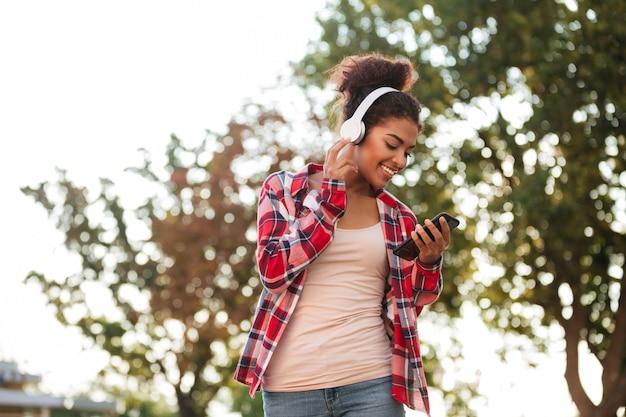 野外を歩いている陽気な若いアフリカ人女性