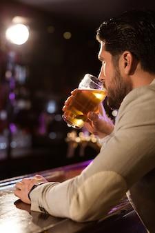 ビールのグラスを持って男のクローズアップ