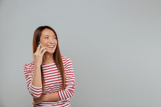電話で話している若いアジア女性を笑ってください。