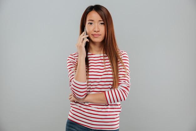 Грустная молодая азиатская женщина разговаривает по телефону