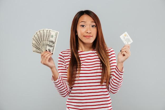Довольно молодая азиатская дама держа деньги и кредитную карточку.