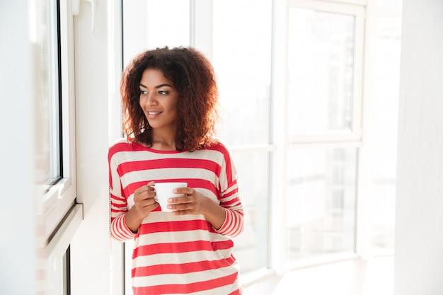 コーヒーを飲みながら笑顔のアフリカの女性