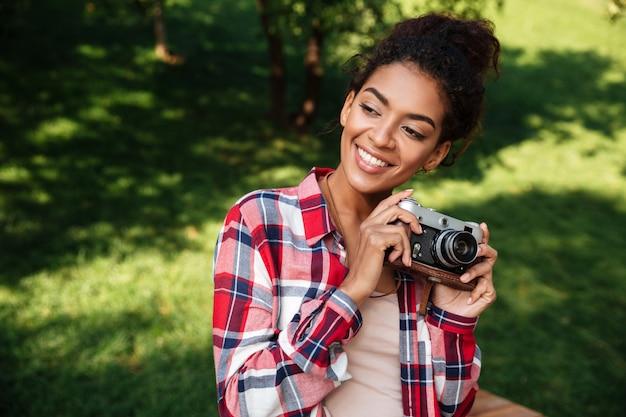 公園の屋外に座っているアフリカの女性写真家。
